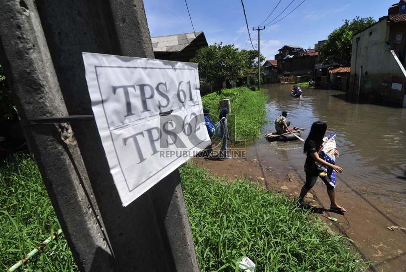 Tanda tempat pemungutan suara (TPS) terpasang diwilayah yang terkena banjir  di Cieunteung, Kabupaten Bandung, Rabu (9/12). (Republika/Septianjar Muharam)