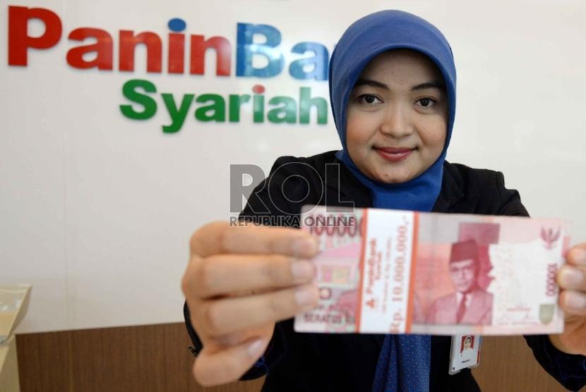 Teller menghitung uang rupiah di Banking Hall Bank, Jakarta, Senin (27/4).  (Republika/ Yasin Habibi)