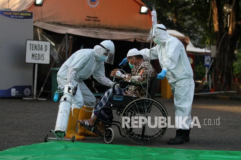 Tenaga kesehatan membantu seorang pasien COVID-19 usai pelaksanaan shalat Idul Fitri di halaman Rumah Sakit Lapangan Indrapura (RSLI) di Surabaya, Jawa Timur, Kamis (13/5/2021). Pelaksanaan shalat Idul Fitri di RS Lapangan Indrapura tersebut diikuti sekitar 30 pasien dari Pekerja Migran Indonesia (PMI) dan puluhan tenaga kesehatan.