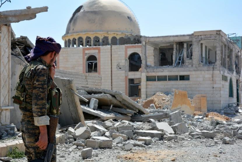 Tentara berpatroli di sebelah bangunan yang hancur di Kota Raqqa, Suriah.