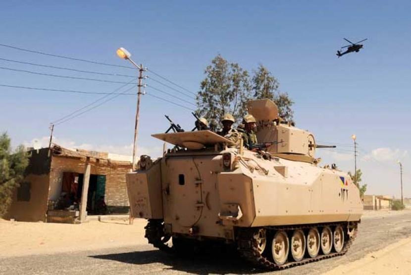 Tentara Mesir berpatroli di sebuah kendaraan lapis baja yang didukung oleh helikopter tempur di Sheikh Zuweyid, Sinai Utara, Mesir.
