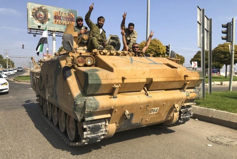 Tentara oposisi Suriah yang didukung Turki mengendarai kendaraan bersenjata di Akcakale, Sanliurfa, tenggara Turki, Jumat (18/10).