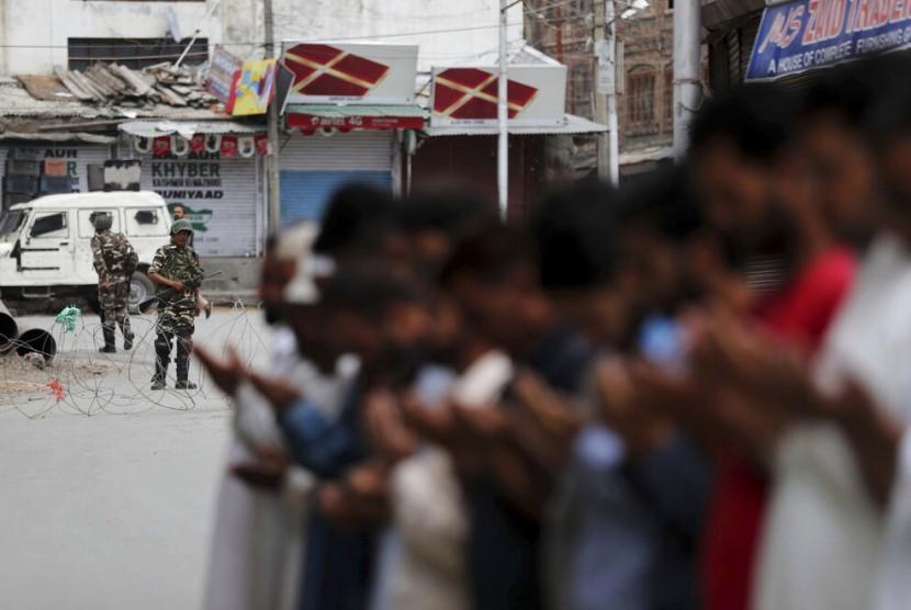 Tentara paramiliter India berjaga saat Muslim Kashmir menunaikan shalat Jumat di jalan di luar masjid setempat saat jam malam di Srinagar, India, Jumat (16/8).