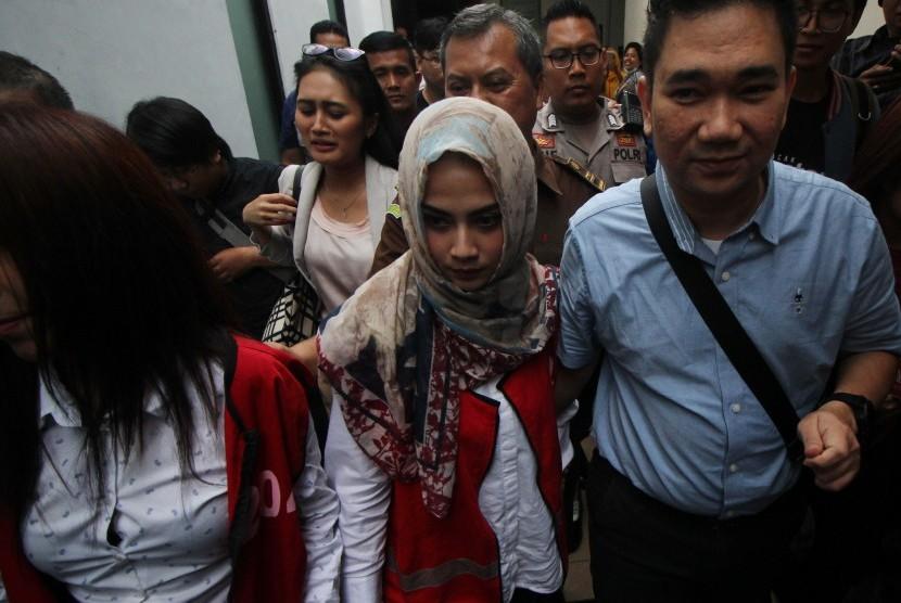 Terdakwa kasus dugaan penyebaran konten asusila Vanessa Angel (tengah) didampingi kuasa hukumnya berjalan keluar seusai sidang lanjutan di Pengadilan Negeri (PN) Surabaya, Jawa Timur, Kamis (16/5/2019).