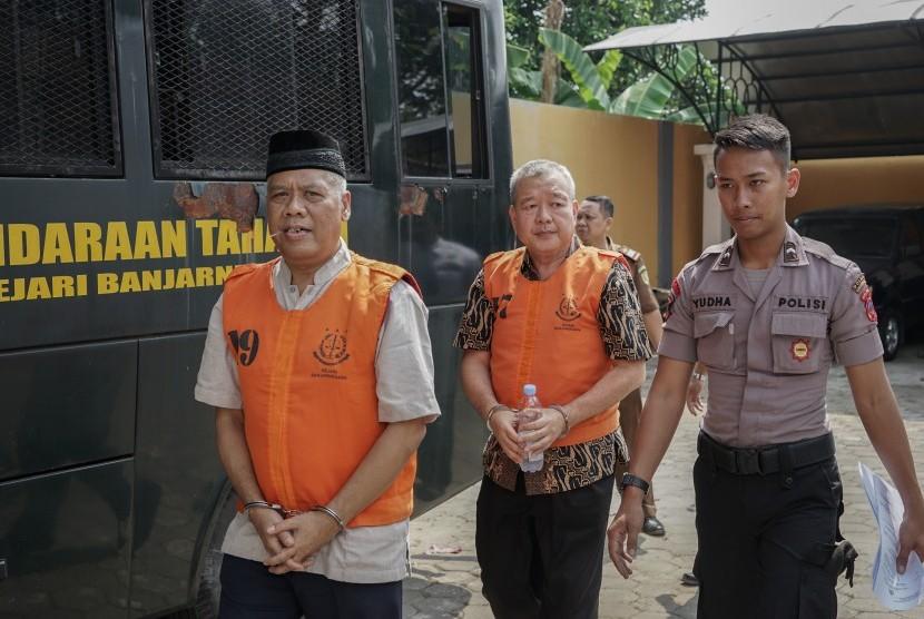 Terdakwa kasus mafia bola Dwi Irianto alias Mbah Putih (kiri) dan Tjan Ling Eng alias Johar Ling Eng (tengah), dikawal petugas menuju ruang sidang di Pengadilan Negeri Banjarnegara, Jateng, Senin (24/06/2019).