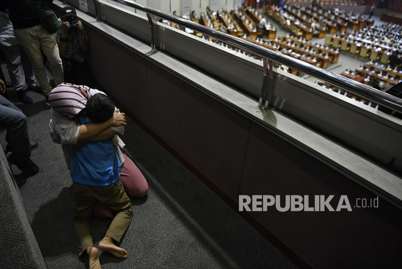Terpidana kasus pelanggaran Undang-Undang Transaksi dan Informasi Elektronik (UU ITE), Baiq Nuril Maknun memeluk putranya usai pengesahan amnesti untuk dirinya pada rapat paripurna DPR di Kompleks Parlemen Senayan, Jakarta, Kamis (25/7/2019).