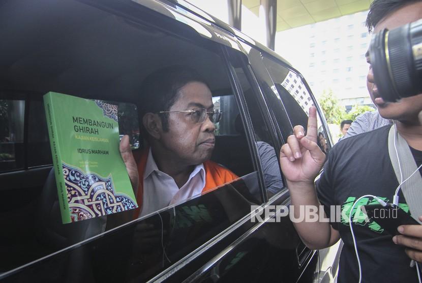 Tersangka kasus dugaan suap proyek pembangunan PLTU Riau-1, Idrus Marham, membagikan buku seusai menjalani pemeriksaan di gedung KPK, Jakarta, Jumat (28/12/2018).