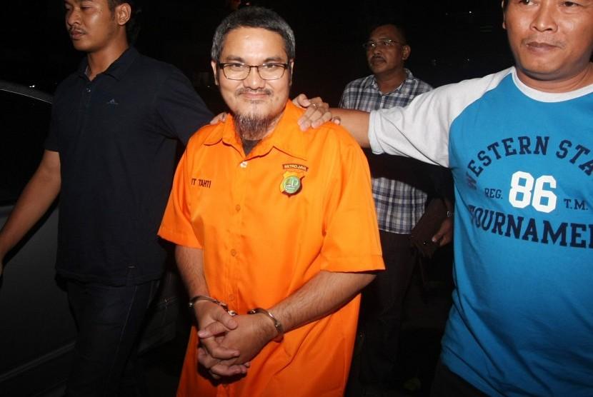 Tersangka kasus dugaan ujaran kebencian di media sosial, Jonru Ginting (tengah) berjalan keluar dari ruang penyidikan dengan pengawalan petugas kepolisian usai menjalani pemeriksaan lanjutan di Ditreskrimsus Polda Metro Jaya, Jakarta, Minggu (1/10).