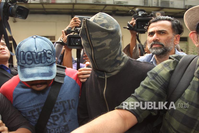 Tersangka kasus narkotika, Axel Matthew Thomas (tengah/mengenakan penutup wajah) didampingi ayahnya, Jeremy Thomas, tiba di rutan narkoba Polda Metro Jaya, Jakarta, Rabu (19/7).