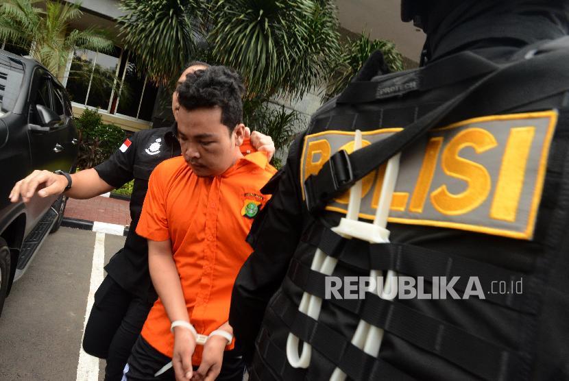 Tersangka kasus pembunuhan satu keluarga HS digiring usai konferensi pers di Polda Metro Jaya, Jakarta, Jumat (16/11).
