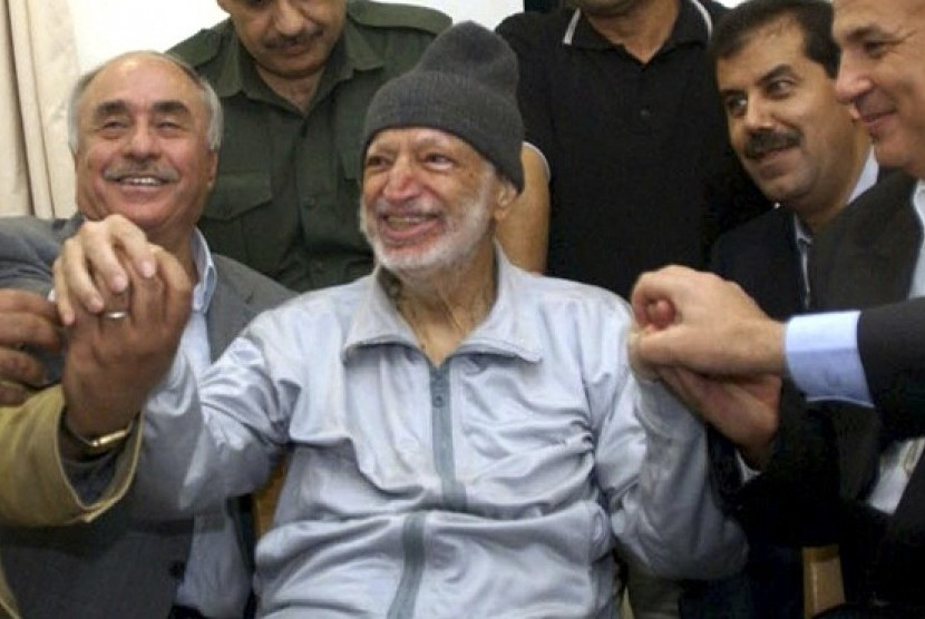 Then Palestinian President Yasser Arafat sits (center) surrounded by doctors from Tunis, Egypt and Jordan in his office in the West Bank City of Ramallah in this October 28, 2004 (file photo).