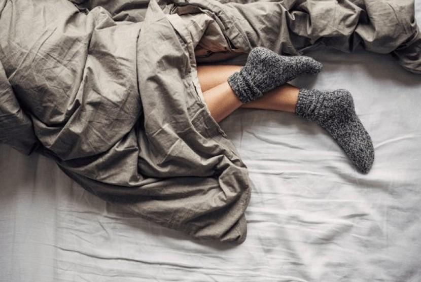 Tidur dengan mengenakan kaus kaki.
