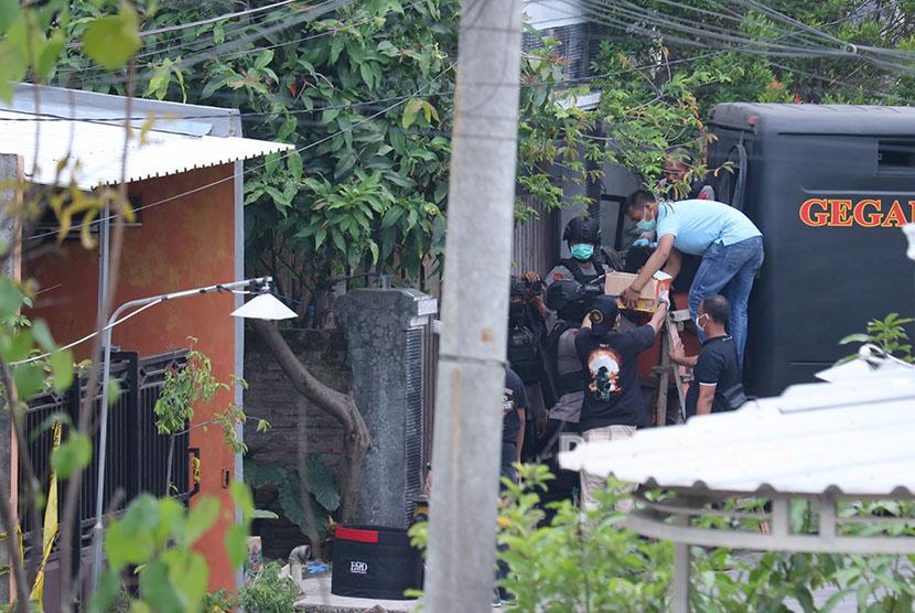 Tim Densus 88 memasukkan kardus yang diduga berisi peledak ke dalam tabung pengaman saat dilakukannya penggeledahan di kediaman terduga pelaku bom bunuh diri Polrestabes Surabaya, di Tambak Medokan Ayu, Surabaya, Jawa Timur, Selasa (15/5).