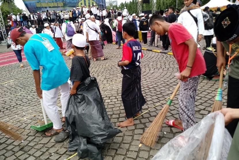 Tim Divisi Kebersihan membersihkan sampah di area Reuni Aksi 212.