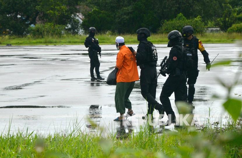 Detasemen Khusus (Densus) 88 Antiteror Polri menggiring tersangka teroris saat akan diberangkatkan ke Jakarta di Bandara Sultan Hasanuddin, Kabupaten Maros, Sulawesi Selatan, Kamis (4/2/2021).