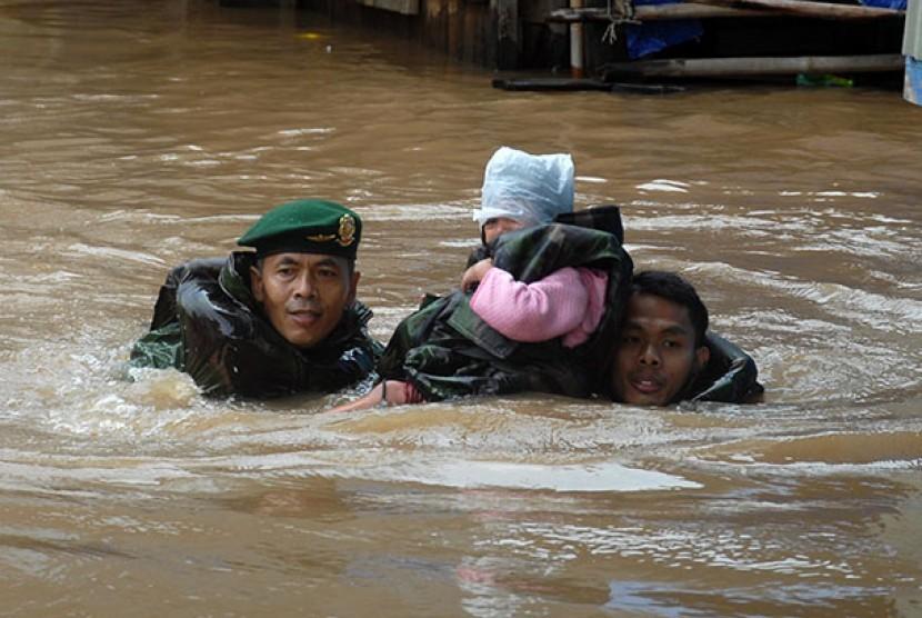 Tim Kostrad mengevakuasi seorang bocah korban banjir