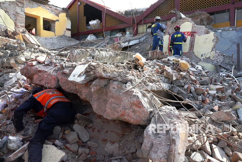 Tim penyelamat berusaha mengevakuasi korban dari bangunan yang runtuh akibat gempa 8,2 SR  di kota Juchitan, Oaxaca, Meksiko,  Sabtu (9/9).