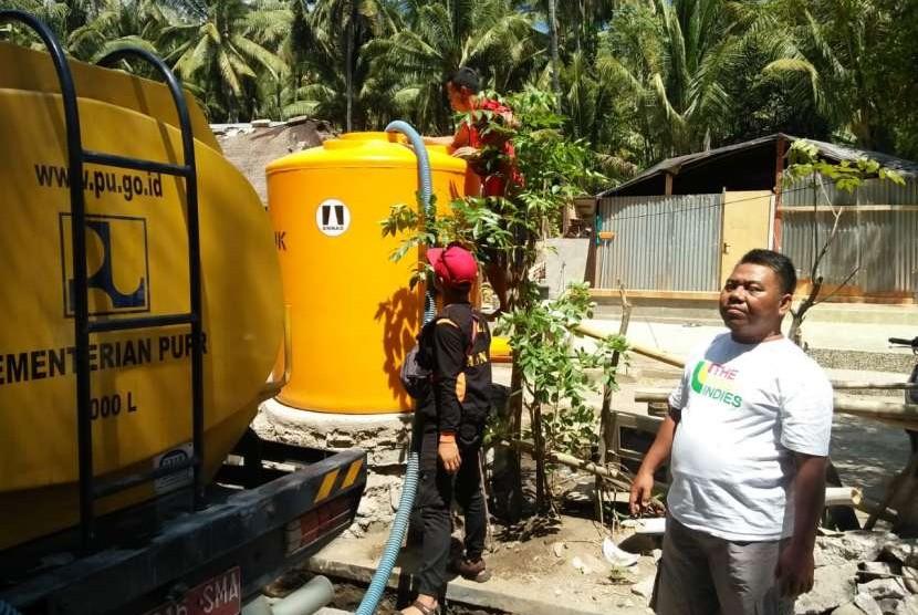 tim relawan Aliansi Nasional Anti Syiah (ANNAS) membantu distribusi air bersih.