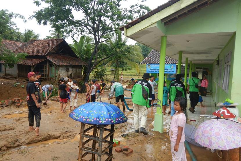 Tim relawan Dompet Dhuafa membantu membersihkan rumah warga pascabanjir.