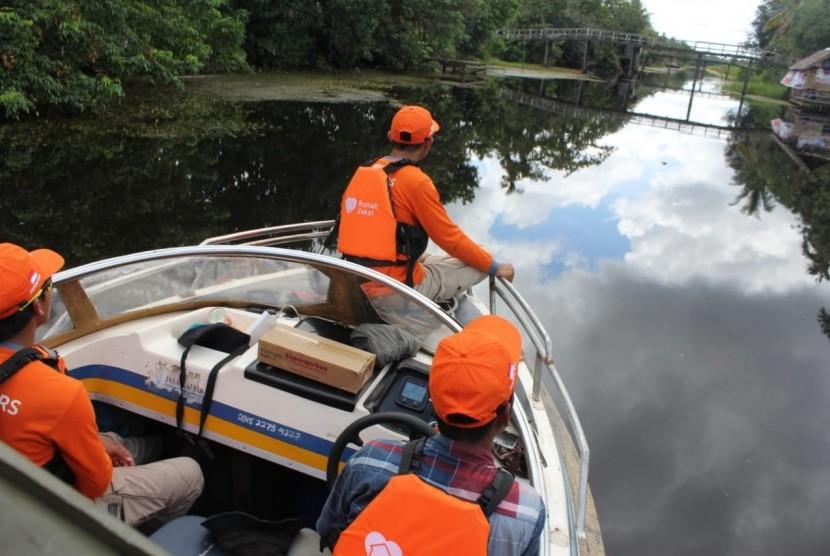 Tim relawan Rumah Zakat membawa bantuan Superqurban untuk warga Desa Sungai Terus.
