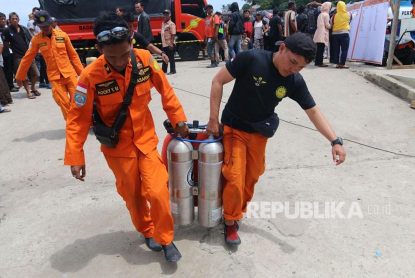 Tim SAR gabungan mengangkat perlengkapan selam saat pencarian korban tenggelamnya KM Sinar Bangun, di Danau Toba, Simalungun, Sumatera Utara, Ahad (24/6).