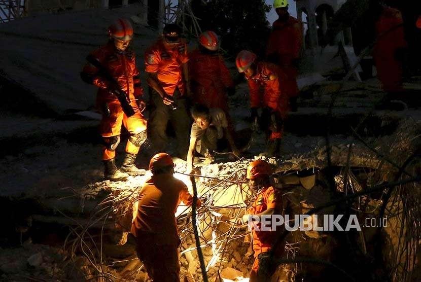 TIm SAR mencari korban selamat dari sebuah mesjid di Lombok Utara, Nusa Tenggara Barat, Senin (6/8). Gempa berkekuatan 7 SR menewaskan 91 korban jiwa dan ratusan luka. Ribuan rumah rusak ringan hingga parah.