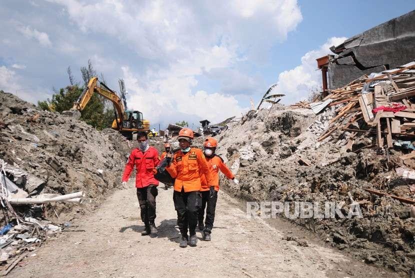 Tim SAR mengevakuasi seorang korban gempa yang tercebur lumpur di Kompleks Perumahan Kelurahan Petobo Palu, Sulawesi Tengah (2/10).