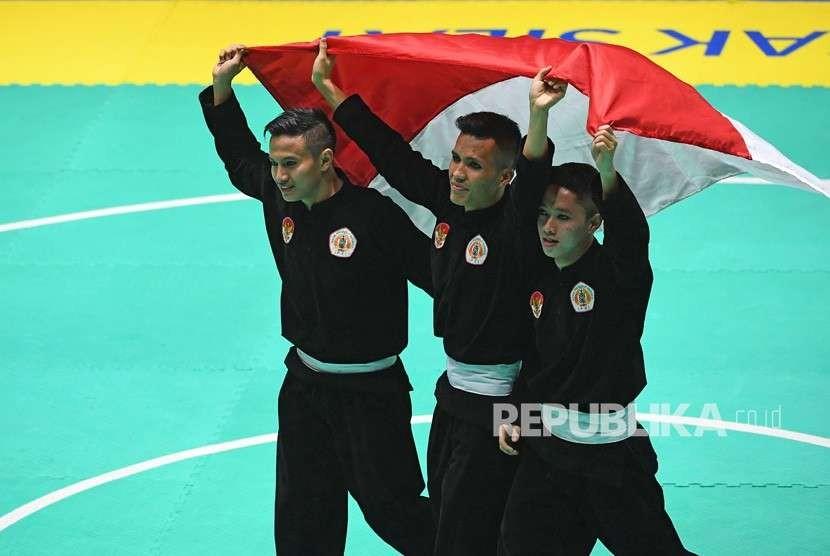 Tim silat Indonesia peraih medali emas Nunu Nugraha (tengah), Asep Yuldan Sani (kiri) dan Anggi Faisal Mubarok (kanan) merayakan kemenangan dengan membentangkan bendera merah putih usai meraih medali emas dalam final beregu putra pencak silat seni Asian Games 2018 di Padepokan Pencak Silat Taman Mini Indonesia Indah (TMII), Jakarta, Senin (27/8).