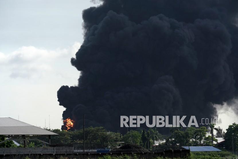 Titik api terlihat di antara asap mengepul dari tanki yang terbakar di area Kilang Pertamina RU IV Cilacap, Jateng, Sabtu (12/6/2021). General Manager Pertamina RU IV Cilacap Joko Pranoto, menyebutkan bahwa saat ini petugas masih berusaha untuk memadamkan titik api di outlet nozel T39-203.