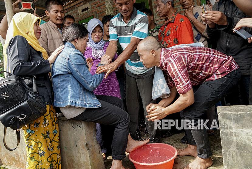 TKW yang hilang selama 18 tahun, Parinah (kedua kiri), dibasuh kakinya oleh anak ketiganya, Nurhamdan (kanan), ketika pulang ke rumah anak pertamanya di Desa Nusawungu, Nusawungu, Cilacap, Jawa Tengah, Kamis (12/4).