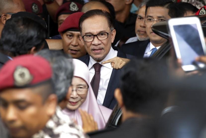 Tokoh reformis Malaysia Anwar Ibrahim dan istrinya Wan Azizah berjalan keluar dari rumah sakit di Kuala Lumpur, Malaysia, Rabu (16/5). Anwar dibebaskan dari penahanannya.