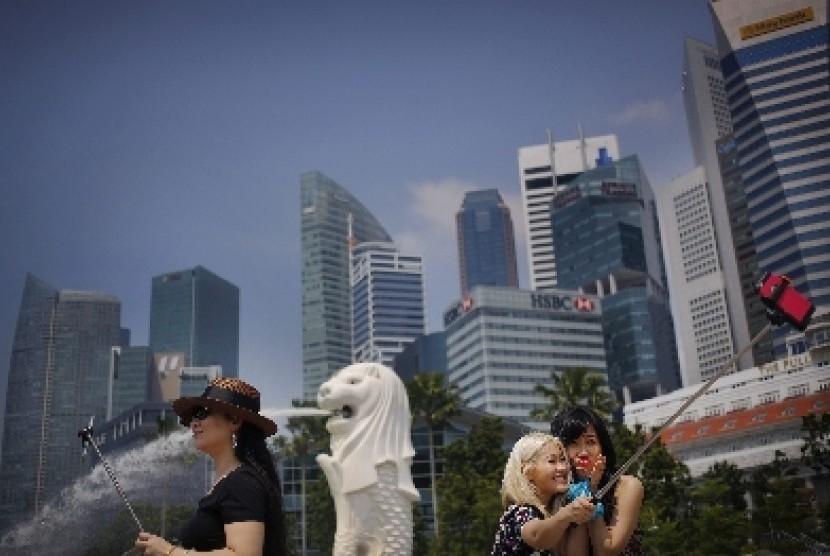 Turis melakukan swafoto dengan latar Patung Merlion, salah satu atraksi wisata populer di Singapura.