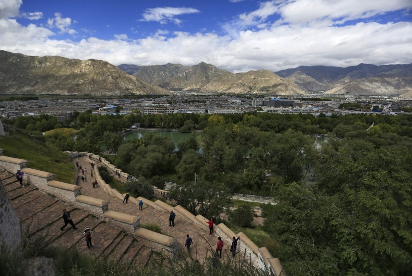 Turis menaiki anak tangga di Istana Potala dengan pemandangan Kota Lhasa, Tibet.