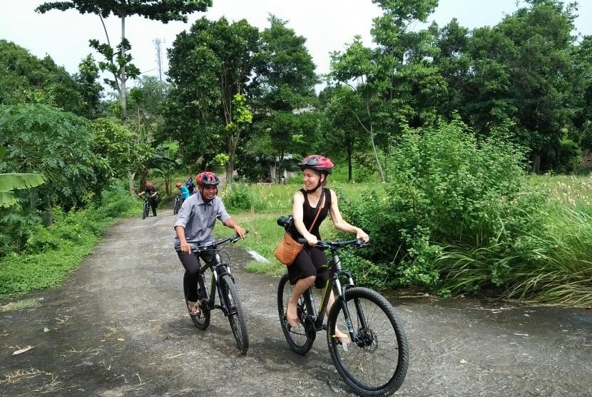 Turis menikmati bersepeda di Desa Bilabante, Lombok.