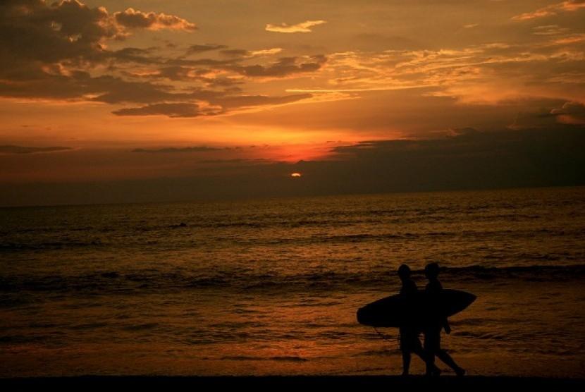 Two surferers pass during a sunset at Kuta beach, Bali. (illustration)