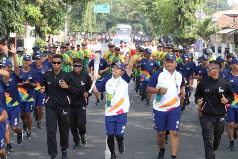Udjo (kiri) membawa obor Asian Games 2018 saat Torch Relay Asian Games 2018 di Purwakarta, Jumat (10/8).