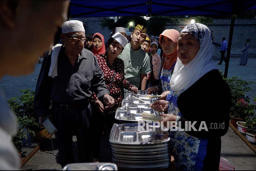 Umat Islam di Masjid Niujie Beijing, Cina berkumpul menunggu antrean makan saat buka bersama, Jumat (2/6).