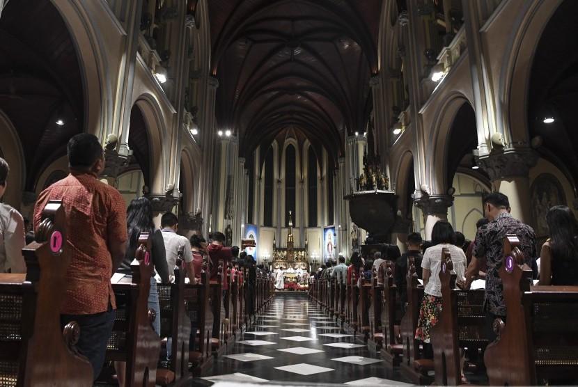 Umat Katolik melaksanakan misa malam Natal di Gereja Katedral, Jakarta, Senin (24/12).