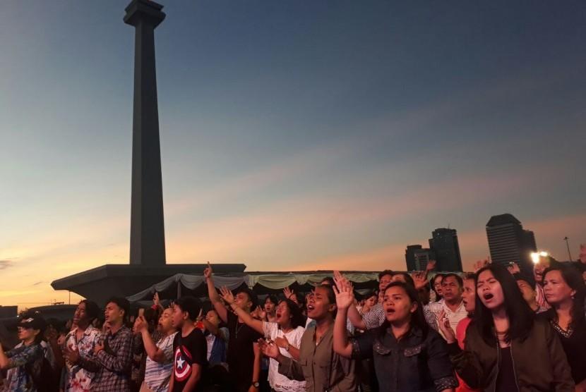 Umat Kristiani dari jemaat GBI Glow Fellowship Center, Thamrin, Jakarta Pusat merayakan Paskah di Monumen Nasional (Monas), Jakarta Pusat, Ahad (1/4).