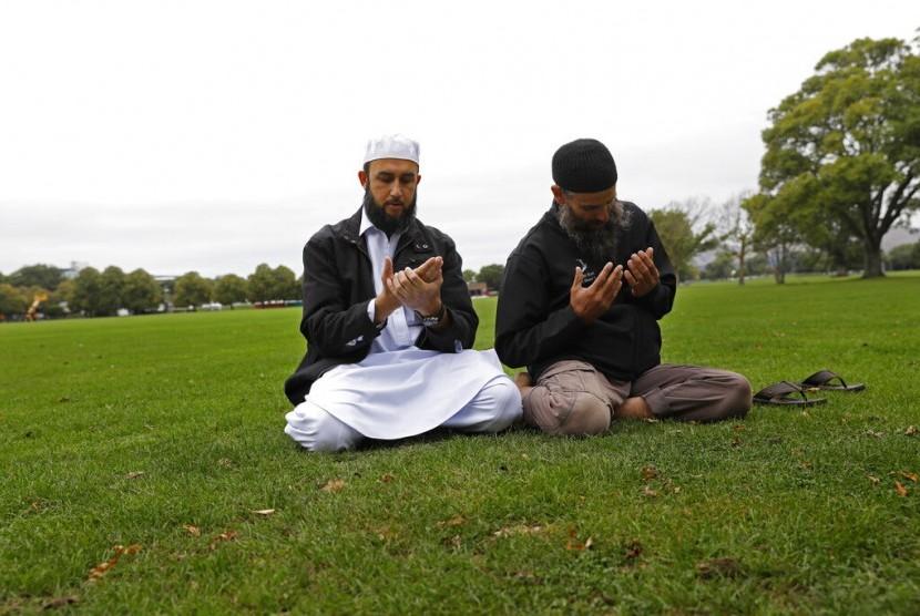 Umat Muslim berdoa di taman di luar Masjid Al Noor di Christchurch, Selandia Baru, Senin (18/3).