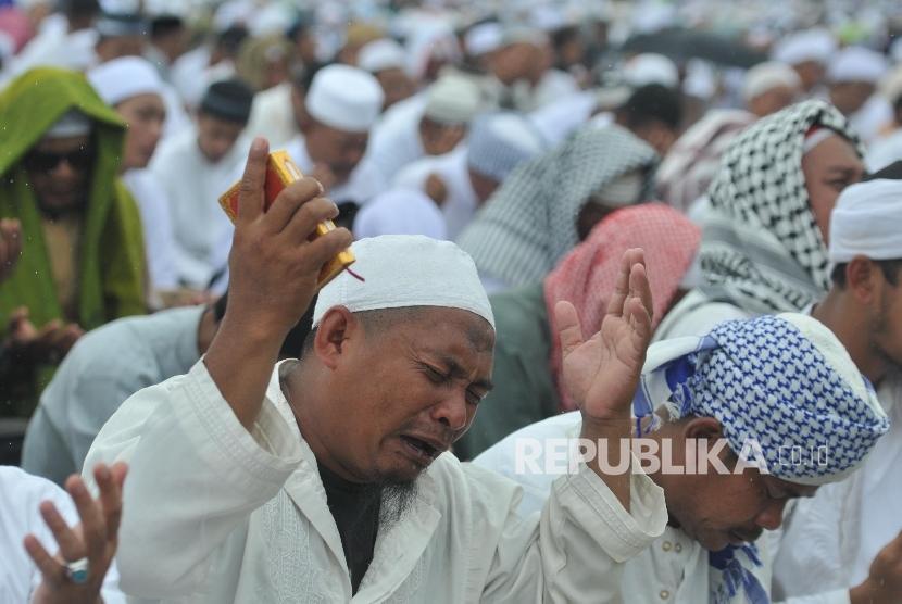 Umat muslim berdoa ditengah guyuran hujan saat mengikuti aksi damai di kawasan Monas, Jakarta, Jumat (2/12).