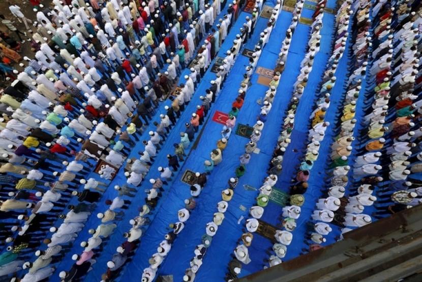 Umat Muslim melaksanakan shalat id di tepi rel kereta api di Mumbai, India, (18/7).