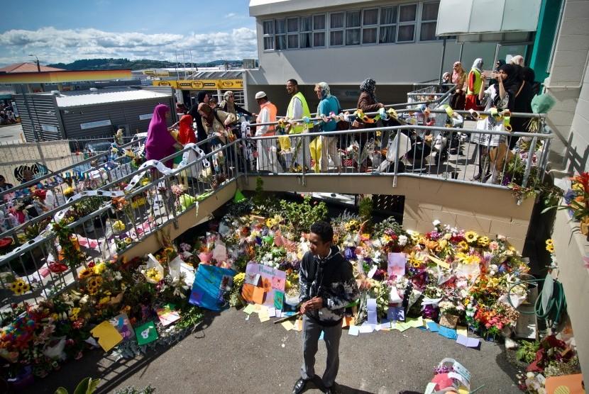 Umat muslim melintasi karangan bunga yang diletakkan warga di depan Masjid Wellington saat pelaksanaan salat Jumat pertama pascapenembakan di dua masjid kota Christchurch pada Jumat (15/3) di Kilbirnie, Wellington, Selandia Baru, Jumat (22/3/2019).