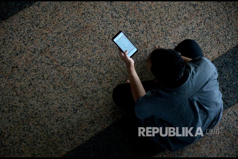 Hikmah Larangan Puasa di Hari Jumat. Umat muslim membaca Alquran digital dengan menggunakan telepon pintarnya.