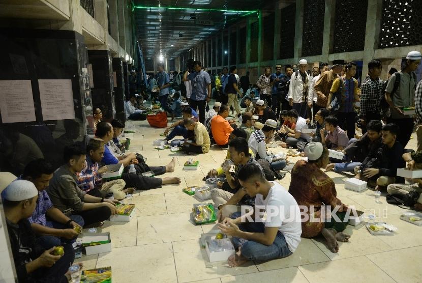Umat Muslim menanti berbuka puasa pada hari pertama bulan suci Ramadan di Masjid Istiqlal, Jakarta.