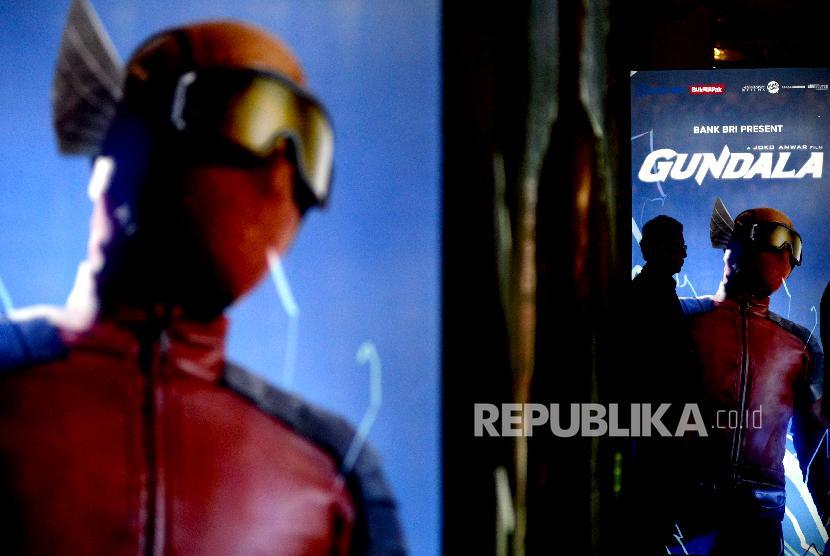 Undangan melintas dekat neon box Gundala saat gala premiere film Gundala di Epicentrum, Kuningan, Jakarta, Rabu (28/8). Setelah melalui proses pembuatan dua tahun, Gundala siap tayang di bioskop seluruh Indonesia Kamis (29/8).