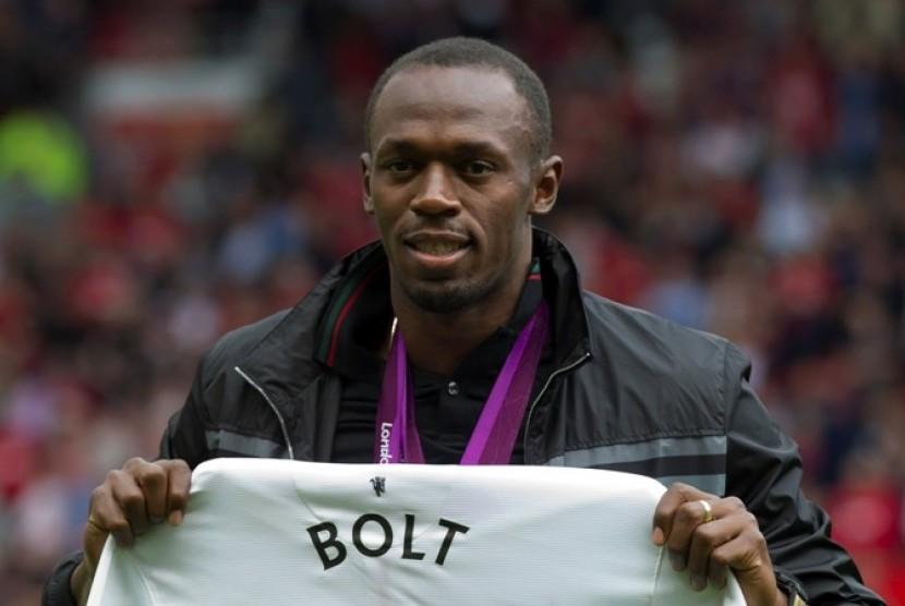 Usain Bolt memegang jersey Manchester United bertuliskan namanya