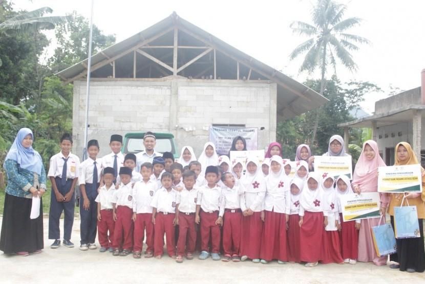 Ustaz dan ustazah bersama siswa sekolah madrasah.