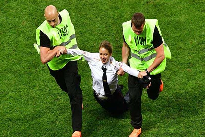 Veronika Nikulshina saat diamankan petugas setelah menerobos ke lapangan saat laga final Piala Dunia 2018.