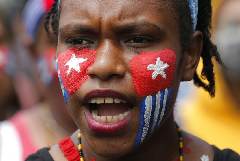 Wajah pengunjuk rasa digambar bendera kejora di aksi dekat Istana, Rabu (28/8). Aksi dilakukan oleh mahasiswa Papua Barat sebagai protes atas insiden rasis.